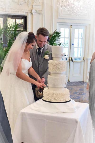 Maria and Adam cutting their cake at Trump Turnberry