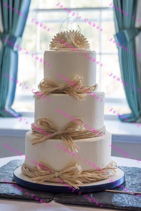 Wedding cake in smooth butter-cream with raffia bows