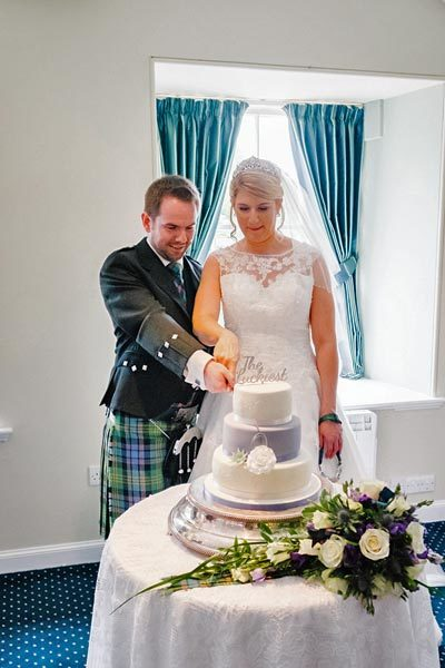 Carly and Andy cutting the wedding cake at New Lanark Mill Hotel